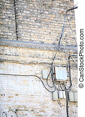 Electric controller box and tangle of cables on brick wall