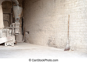 electric corn mill and wooden broom at the wall - electric...