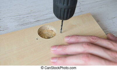 Electric drill drilling a hole in timber. Repair of a...