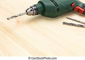 Electric drill on wooden floor background