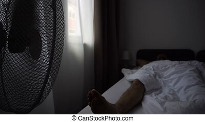 Electric Fan Blowing Air On Man Sleeping In Hotel Room Bed