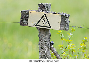 Electric fence in old style with electrical sign
