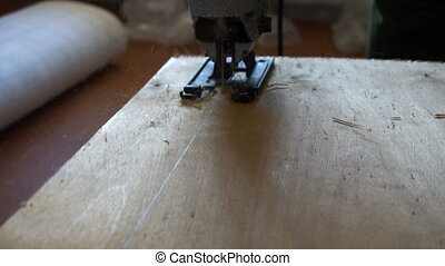 Electric fretsaw is sawing plywood. Close-up.