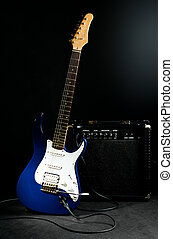 electric guitar and combo amplifier on black background