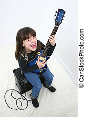 Electric Guitar Girl - Seven year old girl sitting on an...