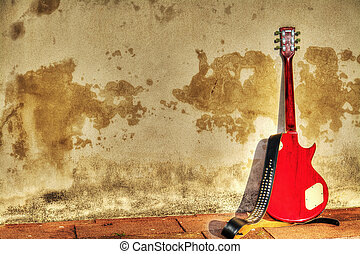 electric guitar leaned on a rustic wall in hdr
