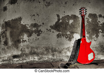 electric guitar leaned on a rustic wall in selective desaturatio
