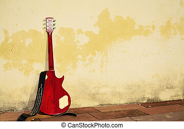 electric guitar leaned on a rustic wall