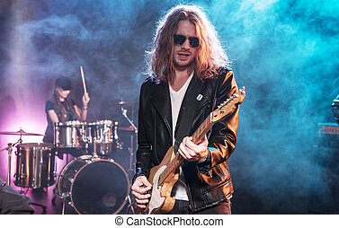 Electric guitar player with rock and roll band performing...