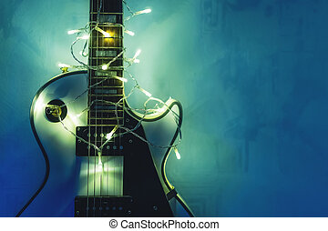 Electric guitar with lighted garland on dark blue...