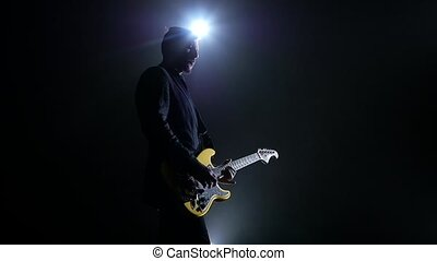 Electric guitar yellow color. Man performs a concert. Slow motion