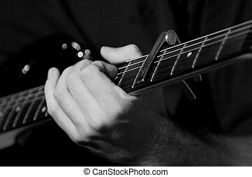 A close-up black and white shot of a hand on a fretboard