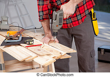 Electric Hand Drill - A male using an electric hand drill on...