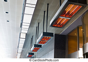 Electric heater with halogen coils at front gate of hotel