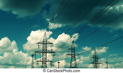electric high voltage pylon against sky, time lapse