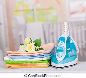 Electric iron and colorful towels on background of ironing room.