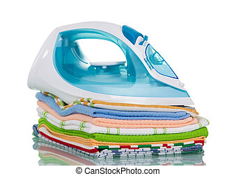 Electric iron stands on bale of ironed kitchen towels, isolated on white