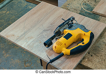 Electric jig saw cuts the workpiece from chipboard for furniture