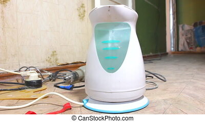 Electric kettle boils water. The kettle is on the floor,...