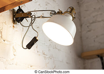 Electric lamp on a white brick wall