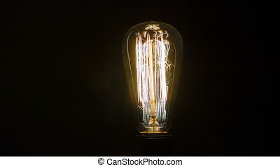 Give the light. Electric light bulb standing isolated on black background and blinking while switching on