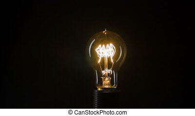 Out of order. Electric light bulb standing isolated on black background while blinking