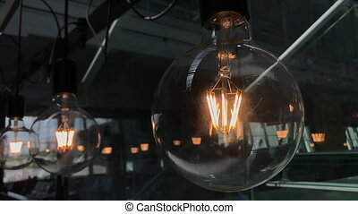 Bright halogen electric light bulbs flickering under the ceiling. Close-up shot