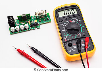 Electric multimeter with red and black probe, display indicating zero, with printed circuit board. Isolated on a white background with a clipping path.