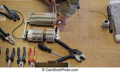 Electric on the desktop screwdriver fastens a wire to the switchboard.