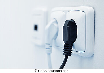 electric plug in a socket closeup. Small shallow DOF
