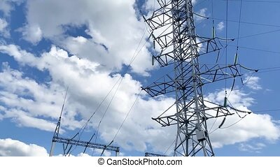 Electric pole with high voltage wires close up against a blue sky