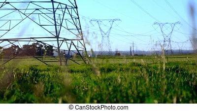 High voltage electric poles on farmland 4K 4k