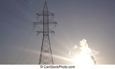 Electric power transmission line support and smoking stack against sunset sky