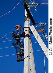 Electric rises to concrete pole - Electrician in overalls...