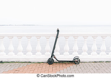 Electric scooter on embankment in front of sea.