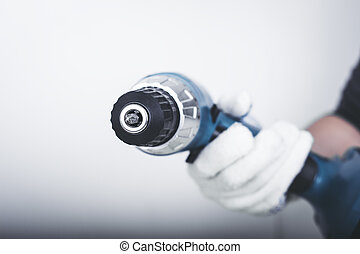 Electric screwdriver in hand at white desk background