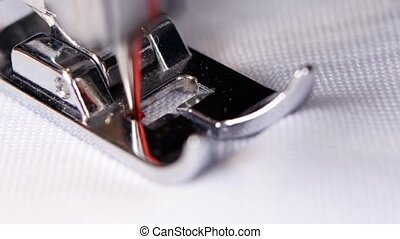 Electric sewing machine makes a red thread stitch. Close up...