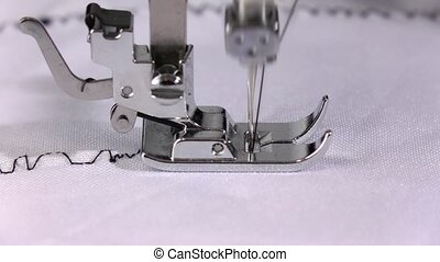 Electric sewing machine makes a seam of black thread. Slow...