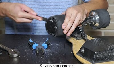 electric skate repair. close-up. locksmith unscrews the...