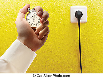 Electric socket and stopwatch in male hand - Electric socket...