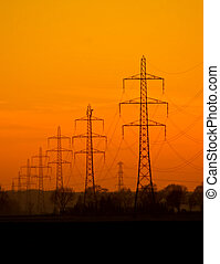 electric sunset - sunset over a field of highvoltage power...