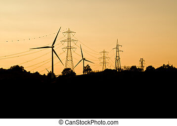 wind turbines and power lines silhouette against the sky at the sunset