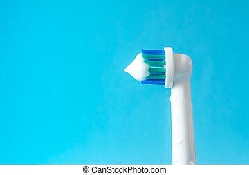 Electric toothbrush with toothpaste closeup on a blue background