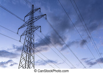 Electric tower and wires against cloudy sky at dusk.