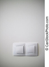Electric two white lighting switchs on concrete wall