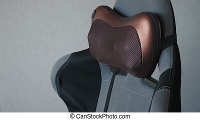 electric vibro massage pillow for neck on the armchair.