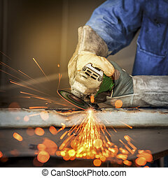 Electric wheel grinding on steel structure by worker in...