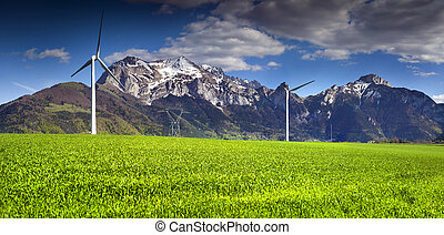 Electric wind turbines in the field of winter wheat in the Alps, near the village of Les Moras, Pellafol, France.