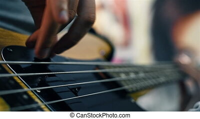 Electrical Bass Guitar Strings With Fingers On It. Close Up