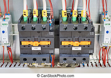 Electrical cables and wires are connected to magnetic starters or contactors.
